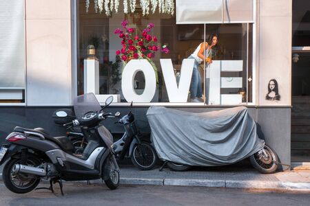 Concept of love. Showcase with a capital LOVE. Young girl decorates showcase, motorcycle on street near window. Conceptual photo. Love theme. Background in rock style. Mona Lisa stencil Banco de Imagens