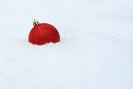 Merry Christmas. Christmas decoration on white snow. Red Christmas ball on white snow. Winter holidays background. Merry Christmas greetings, wallpaper. One bright object on white background Stock Photo