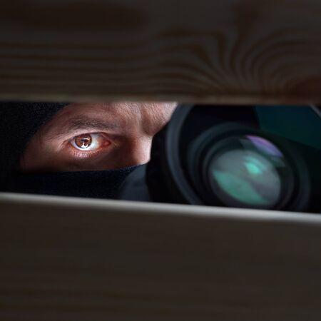 Primer plano masculino del ojo y de la cámara. Grabación a cámara oculta. Detective privado con cámara mira una hendidura. Antecedentes de espionaje. El concepto de espionaje, espionaje, chismes y prensa amarilla