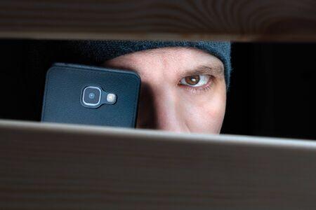 Mans Auge, das durch ein Loch zwischen Holzbrettern schaut. Nahaufnahme. Informationsleck. Spionage-Konzept. Datenschutz Idee. Privatleben. Detektiv mit Kamera. Öffentliches Leben. Dreharbeiten unter dem Tisch