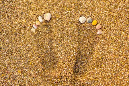 Seashell footprints on the beach. Footprints in the sand. Foot marks on the sand beach with the seashell. Rest by the sea concept. Foot and toes health. Foot and toes procedure