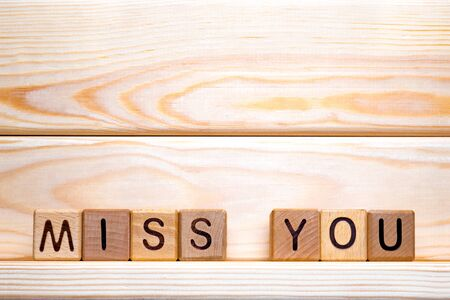 The phrase Miss you. Miss you on wooden cubes. Love theme. Be bored. Be lonely. Valentine's day. Wood letter blocks with words Miss you. Love, positive emotions. Wood cubes with phrase Miss you Banque d'images