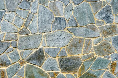 Pared de piedra. Muro de piedras como textura. Muro de piedras. Muro de una fortaleza medieval con piedras principalmente blancas o de colores claros de diferentes tamaños y formas, utilizables como patrón de fondo o para diseños. Foto de archivo