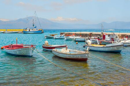 Seascape with sail boats. Mountain range with clouds on background. Pastel colors. Fish industry. Fishing business. Calm weather on the sea. Soft trend colors. Fisherman jetty with mountain on horizon