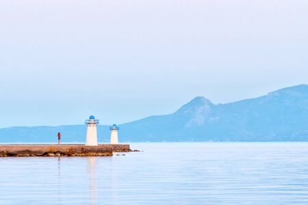 Travel by sea. Tourism concept. Sea lighthouse on mountains background. Beautiful seascape view with lighthouse and mountains. Picturesque scenery. Meditation landscape. Blue colors of the sea