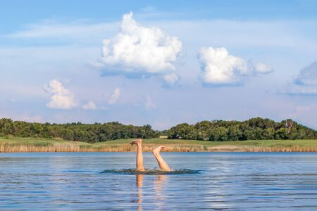 Man legs sticking out from water. Starting swimming season. Funny photo. Enjoying vacation. Bad jump. Reach the bottom of the lake, sea, reaver. Detail of human body, legs under the water with feet up