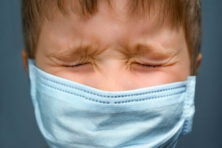 Anxious child and coronavirus COVID-19. Pandemic and kid feelings. Coronavirus disease COVID-19. Anxious boy in medical mask with closed eyes. Quarantine and social distancing. Pediatric, psychology