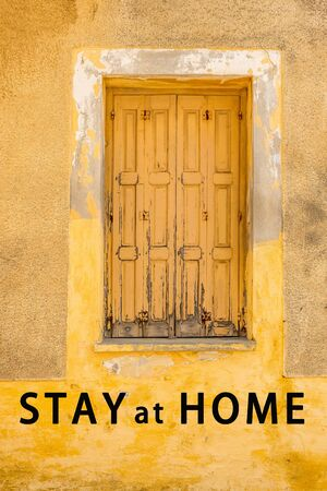 Lockdown rules. Home lockdown background. Restrictions for leaving your house. Closed old shutters on faded yellow wall. Pandemic government toughened measures Stock fotó
