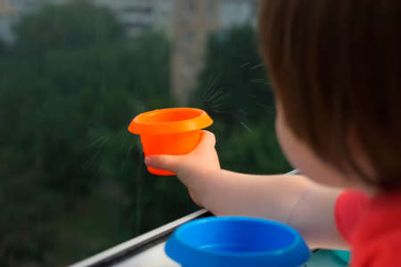Child catching rain drops. Staying at home concept. Rainy day, catching water drops with plate. Happy childhood. Montessori concept. Ecology concept. Happy rainy days. Tactile sensations developing