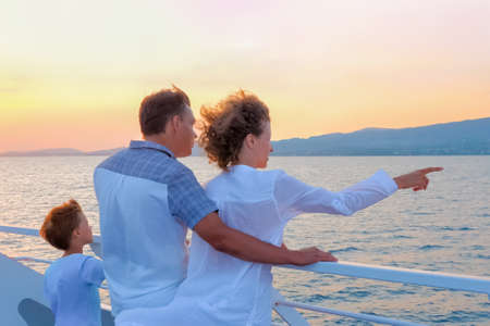 Happy family travels by sea. Family tourism concept. Consumers pinpoint travel. Voyage to Greece. Season stay, short stay of traveling. Woman in white with husband and son on yacht, boat, ship