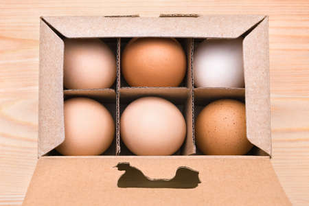 Free grazing of hens. Chicken products in a cardboard box. Exclusive agricultural method. Cardboard box with brown eggs. Organic egg in box. Packing egg. Chicken egg in carton box with hen cut out