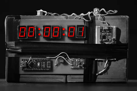 Terrorist threat. Explosives with detonator. Improvised explosive device. Bomb with a red timer on black background. Dynamite is going to explode or detonate per 1 second. Time bomb with clockwork. bw