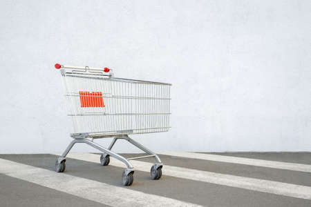 Empty Grocery Cart on the White Wall Store. Trolley at the Supermarket Background. E-commerce. Shopping Concept. Side View. Shopping Cart Trolley Stands near Mall with Copy Space. Black Friday Sale