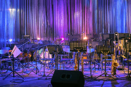Musical Instruments and Sheet Music Standing Ready on a Stage for a Live Performace at Rock or Jazz Concert or Festival in Colourful Lighting. Empty Stage for Orchestra. Online Music Concert or Event