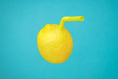 Ripe juicy lemon as a drink in glass with straw or natural freshly lemonade made with real fruit on blue. Vitamin C in yellow lemon fruit minimal concept or homemade lemonade squeezed refreshing drink