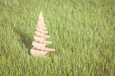 Vintage photo of a Christmas tree made of wood placed in a green garden during a sunny day