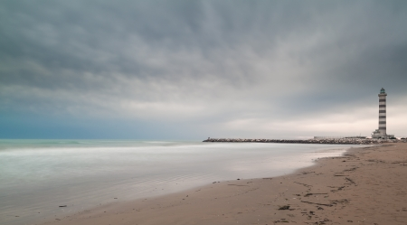 Panorama of smooth sea with cloudy sky and lighthouse in the right  Stock Photo