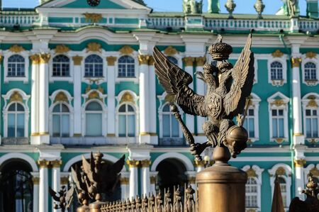 SAINT-PETERSBURG, RUSSIA - MARCH 17, 2015.  Double-headed eagle in the imperial crown on the fence of the Alexander Column on the background of the Hermitage in St. Petersburg focus at the eagle