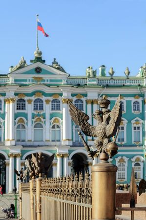 doubleheaded: SAINT-PETERSBURG, RUSSIA - MARCH 17, 2015.  Double-headed eagle in the imperial crown on the fence of the Alexander Column on the background of the Hermitage in St. Petersburg focus at the eagle
