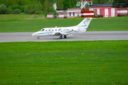 hawker: SAINT-PETERSBURG,RUSSIA -MAY 23,2015.FortAero Baltic Airline Hawker Beechcraft 400XP business jet registration number ES-NXT rides on the runway after landing in Pulkovo International Airport