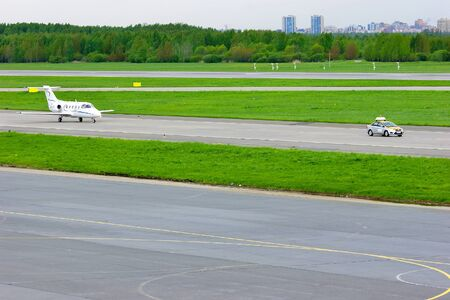 hawker: SAINT-PETERSBURG,RUSSIA -MAY 23,2015.FortAero Baltic Airline Hawker Beechcraft 400XP business jet registration number ES-NXT rides on the runway after Follow Me car in Pulkovo International Airport Editorial