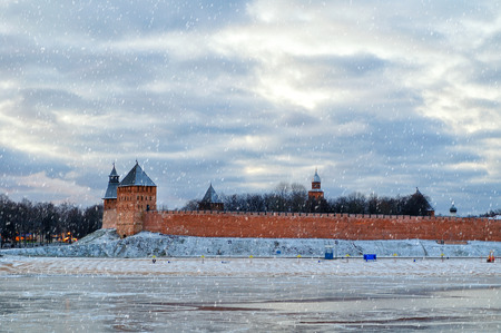 volkhov: Panorama of Novgorod Kremlin defensive walls and river Volkhov in Veliky Novgorod, Russia, in winter cloudy evening with snowfall