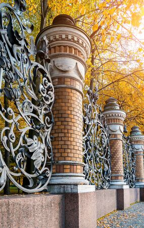 Autumn in St. Petersburg - fence of the Michael Garden in St. Petersburg, Russia in autumn day. Autumn architecture view of St. Petersburg landmark framed by autumn yellowed trees