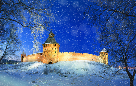 Winter landscape night scene - Novgorod Kremlin fortress in winter night under falling snowflakes. Night view of landmark in Veliky Novgorod, Russia