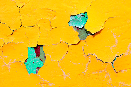 Texture background of bright yellow nad blue peeling paint on the old rough surface