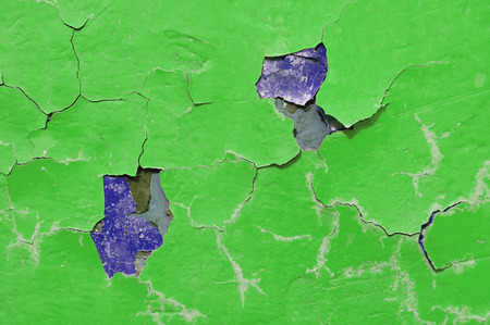 Peeling paint of green and purple colors on the stone background Stock Photo