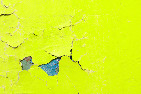 Texture background of bright yellow and blue peeling paint on the old rough surface