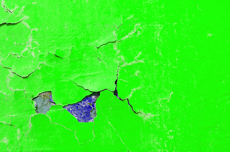 Peeling paint of green and purple colors on the stone texture background