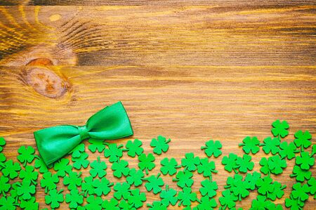 lucky charm: St Patricks Day background - green quatrefoils and bow tie on the wooden background