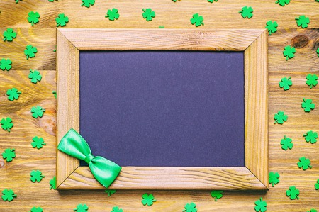 cloverleaf: St Patricks Day background - wooden frame with green bow tie and free space for text and green quatrefoils on the wooden surface Stock Photo