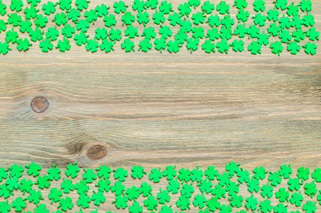 lucky charm: St Patricks Day background - borders of green quatrefoils on the natural wooden surface