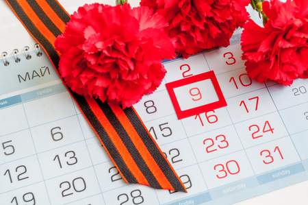 9 May - red carnation with George ribbon lying on the calendar with framed 9 May date Stock Photo