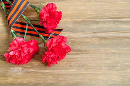 9 May background - red carnations and George ribbon on the wooden background with free space for text