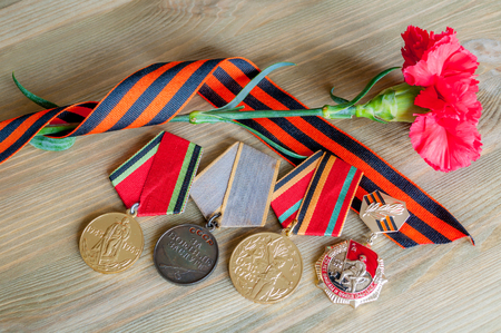 9 May Victory day card with medals of Great patriotic war, red carnations and George ribbon on the wooden background