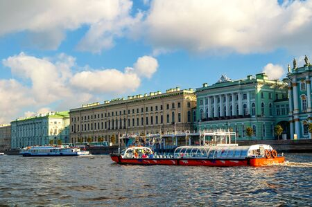 museum visit: ST PETERSBURG, RUSSIA - OCTOBER 3,2016. The Great Old and Small Hermitage buildings on the Palace embankment of Neva river and touristic sailboat floating on the water area in St Petersburg, Russia