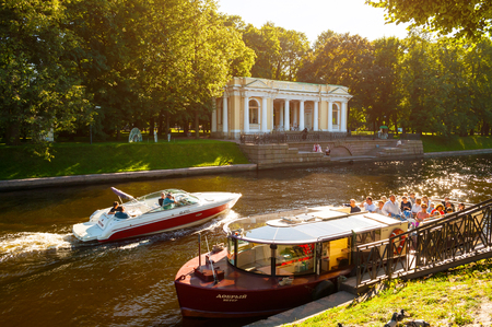 ST PETERSBURG, RUSSIA - AUGUST 15, 2017. Rossi Pavilion in the Michael Garden and the Moika river with floating pleasure boats in St Petersburg, Russia Editorial