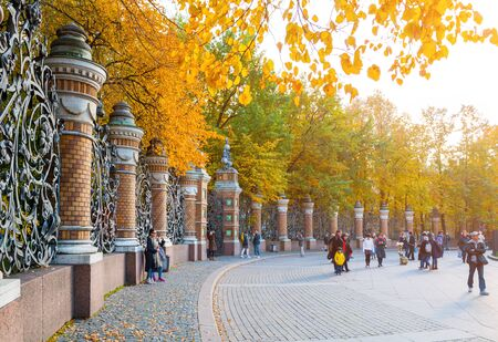 ST PETERSBURG, RUSSIA - OCTOBER 3, 2016. Fence of the Michael Garden in St Petersburg, Russia and tourists walking along