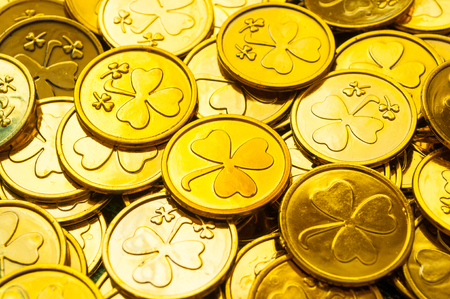 St Patrick's Day background. Golden coins with shamrock under soft sunshine, St Patrick's day concept. St Patricks day festive composition