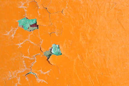 Texture background of bright orange peeling paint on the old rough surface