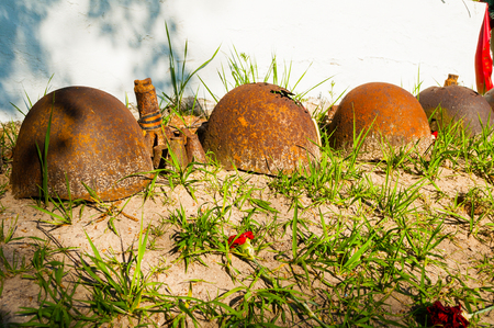 Soviet military helmets with flowers and wreath at the cemetery of fallen soldiers during World War II. Veliky Novgorod, Russia