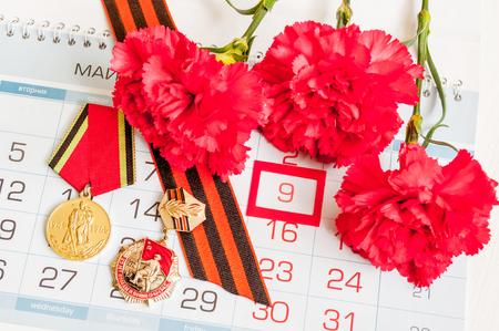 9. Mai - Medaillen des Großen Vaterländischen Krieges mit roten Nelken und Georgsband liegen auf dem Kalender mit gerahmtem 9. Mai-Datum