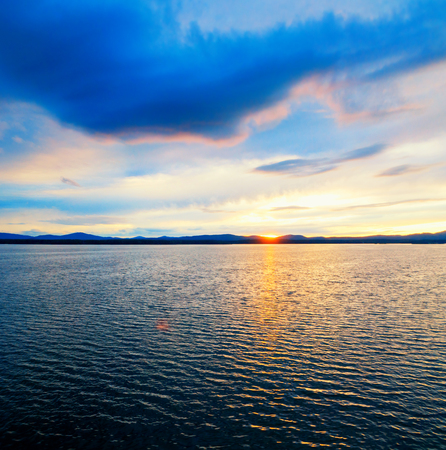 Sea landscape. Sea water surface lit by sunset light. Summer sunny water scene in colorful tones. Sea summer nature with mountain range at the horizon