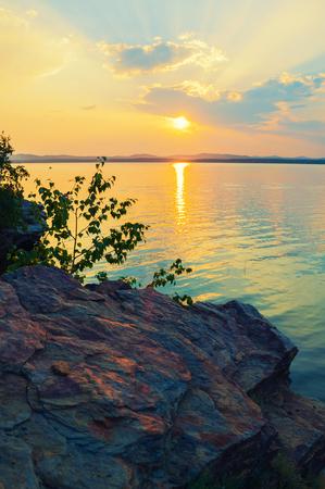 Summer sunset landscape - stone cliff and lake lit by gold sunset light. Colorful summer landscape sunset scene