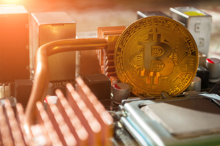 Golden bitcoin on the motherboard. Business concept of digital cryptocurrency. Blockchain technology, bitcoin mining concept