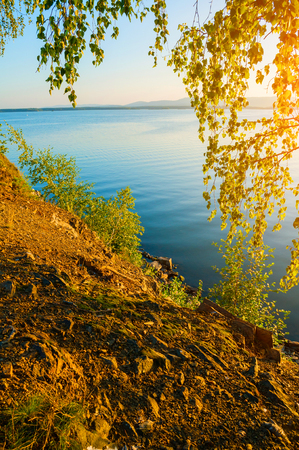 Summer sunset landscape - the Irtyash Lake in Southern Urals, Russia, rippled water surface lit by sunset summer light. Summer sunny water scene
