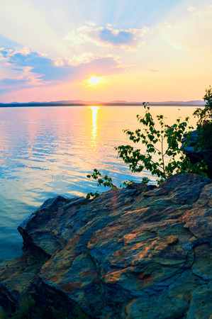 Summer landscape - summer trees at the edge of the stone cliff and lake lit by sunset light. Colorful summer landscape evening scene